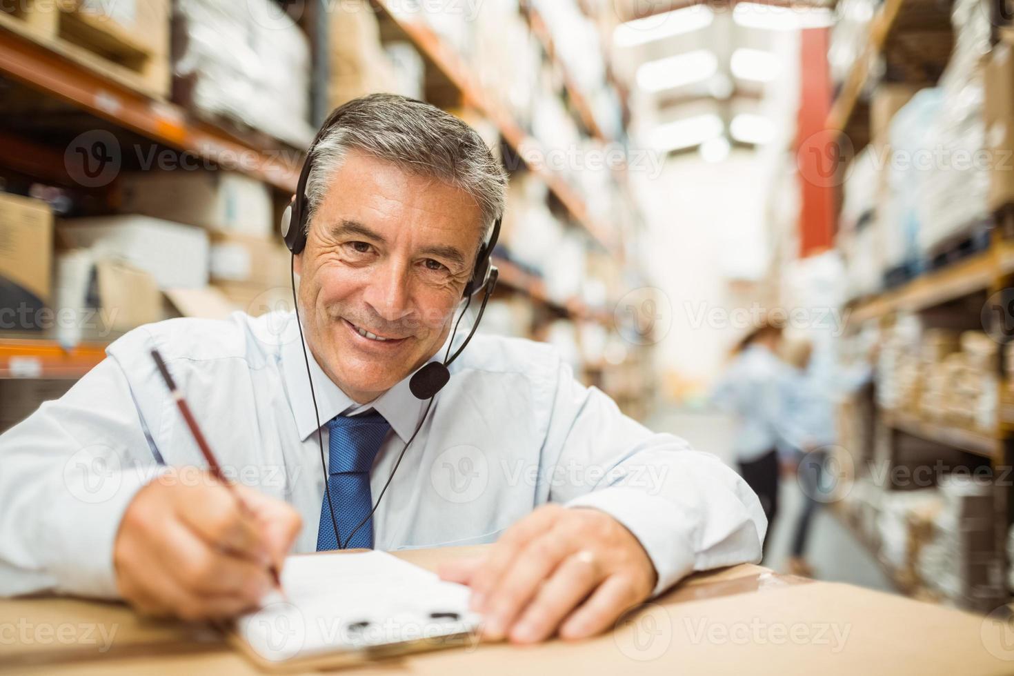 gerente de armazém sorridente, escrevendo na área de transferência foto
