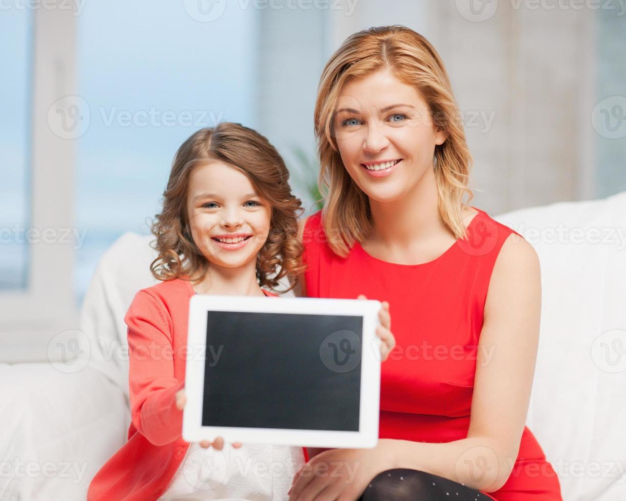 Mother and child holding up blank tablet while sitting photo