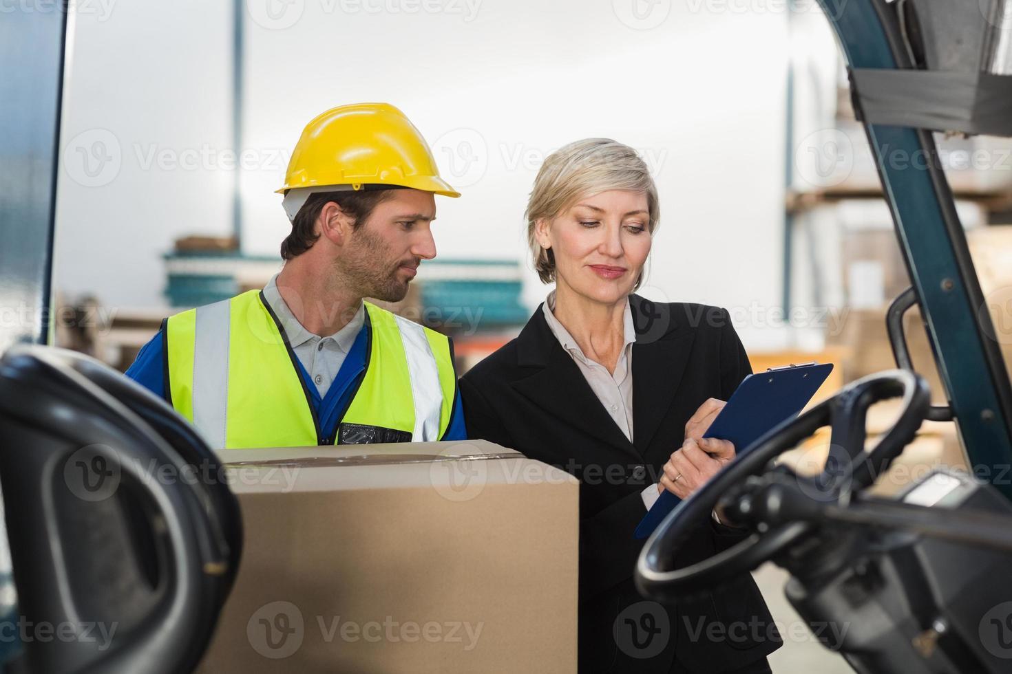 gerente de almacén hablando con conductor de montacargas foto