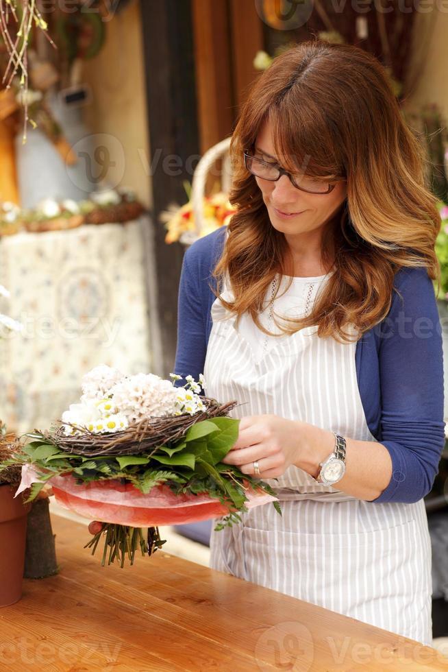 hermosa mujer que trabaja en la tienda de flores foto
