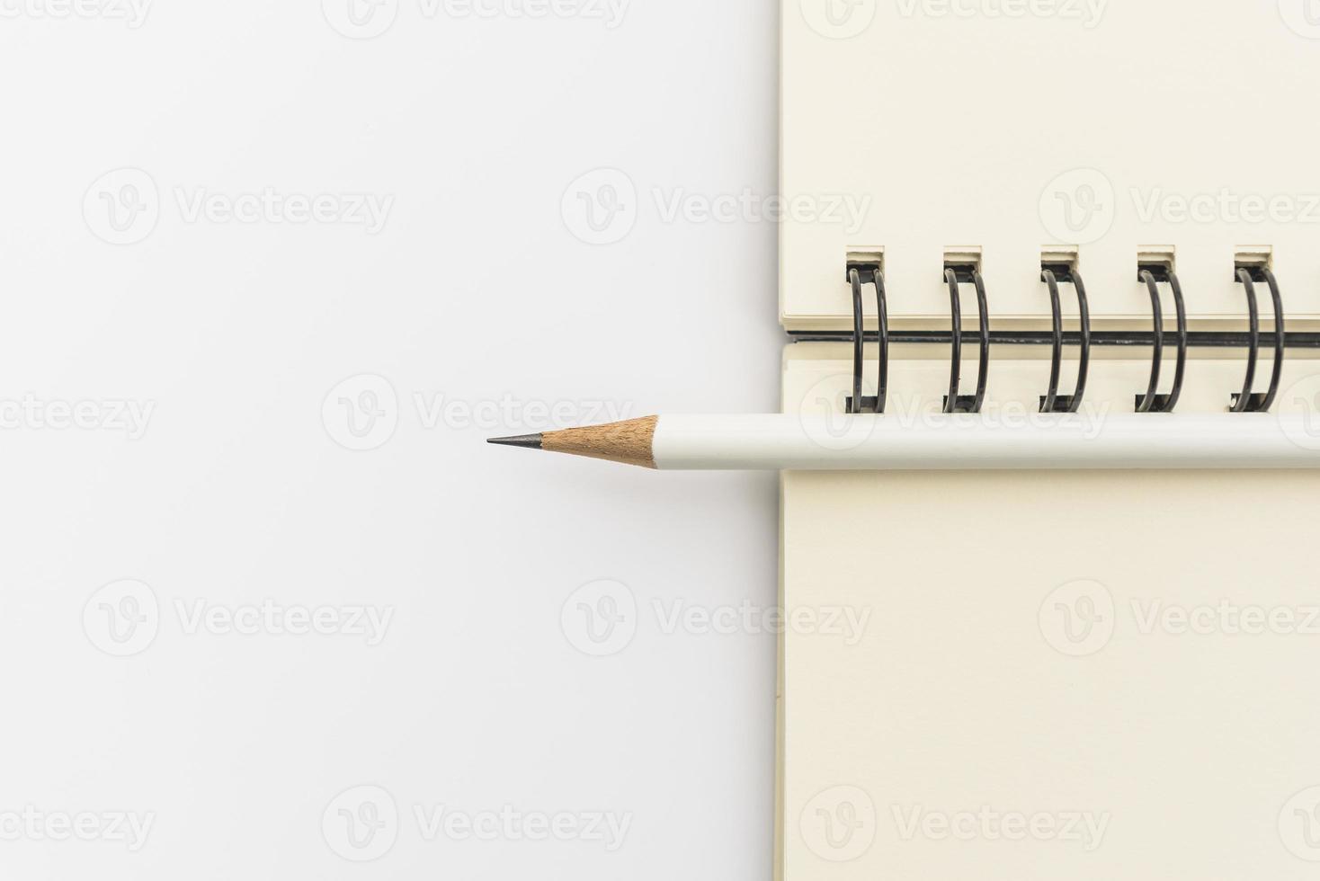 lápiz blanco con cuaderno en blanco foto