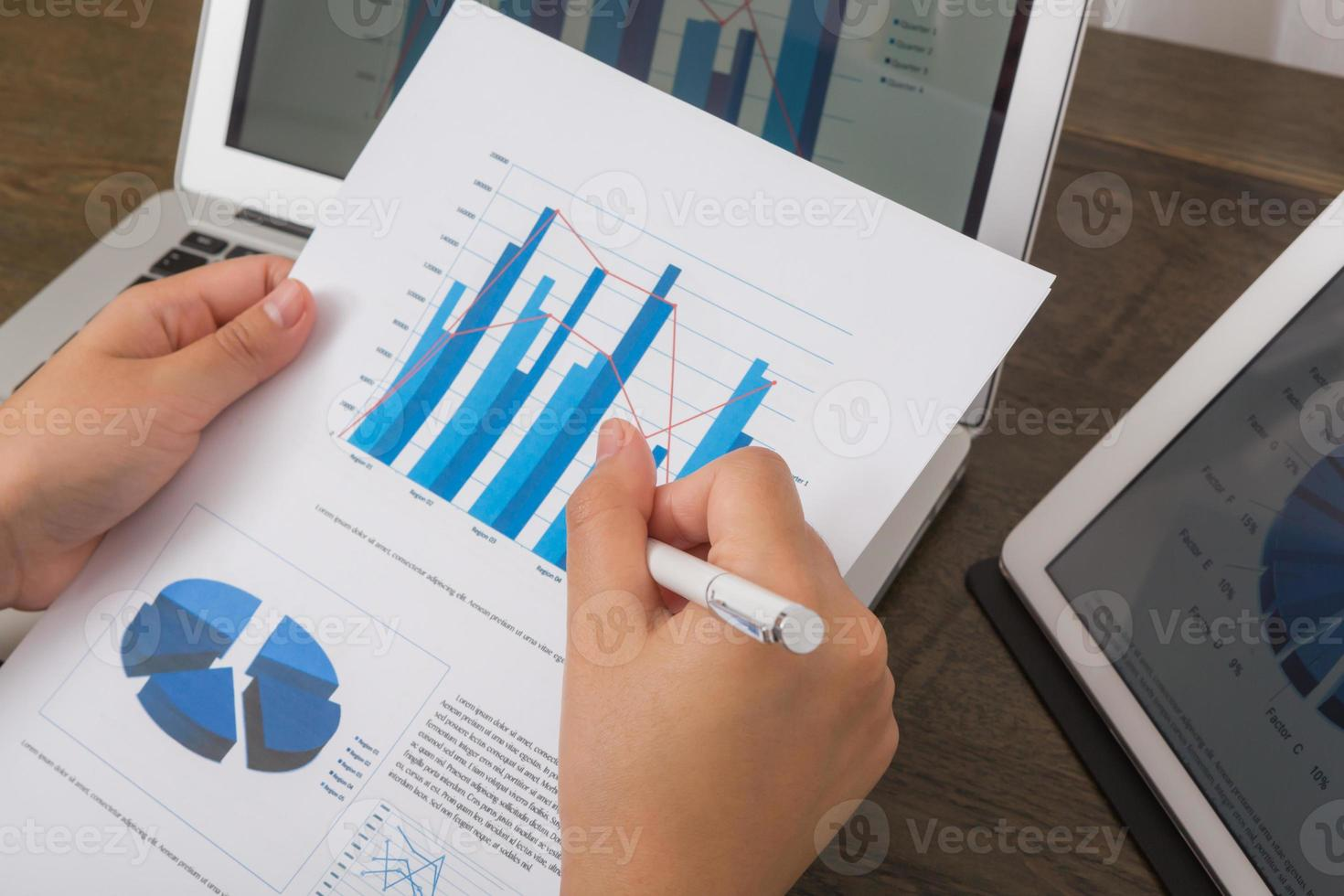 Close-up of business person using digital tablet and laptop with photo