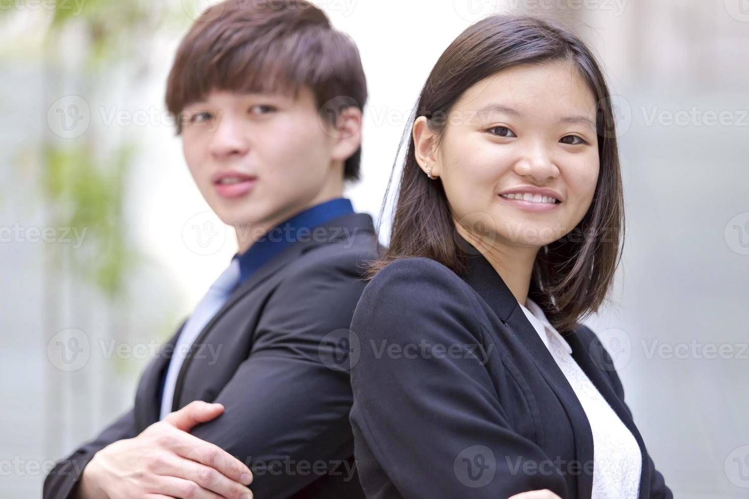 Young female and male Asian business executive smiling portrait photo