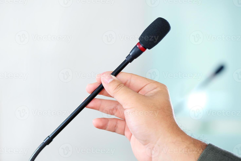 Mano sujetando el micrófono de la conferencia en la sala de reuniones foto