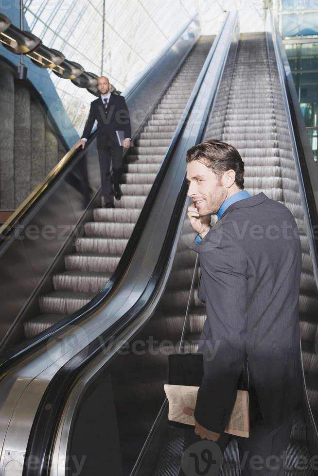Business people on escalator business man using mobile phone photo