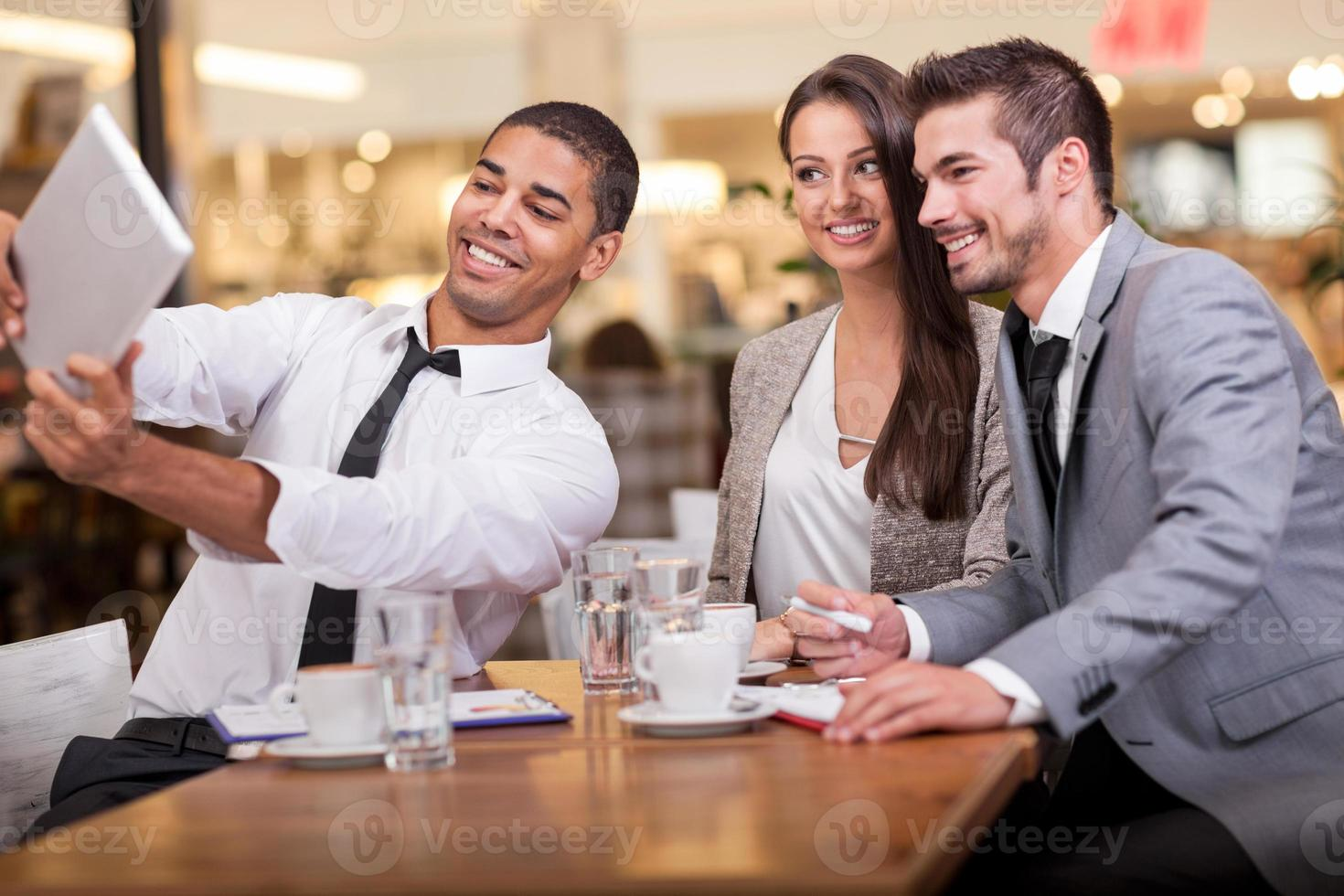 business people taking selfie in restaurant photo