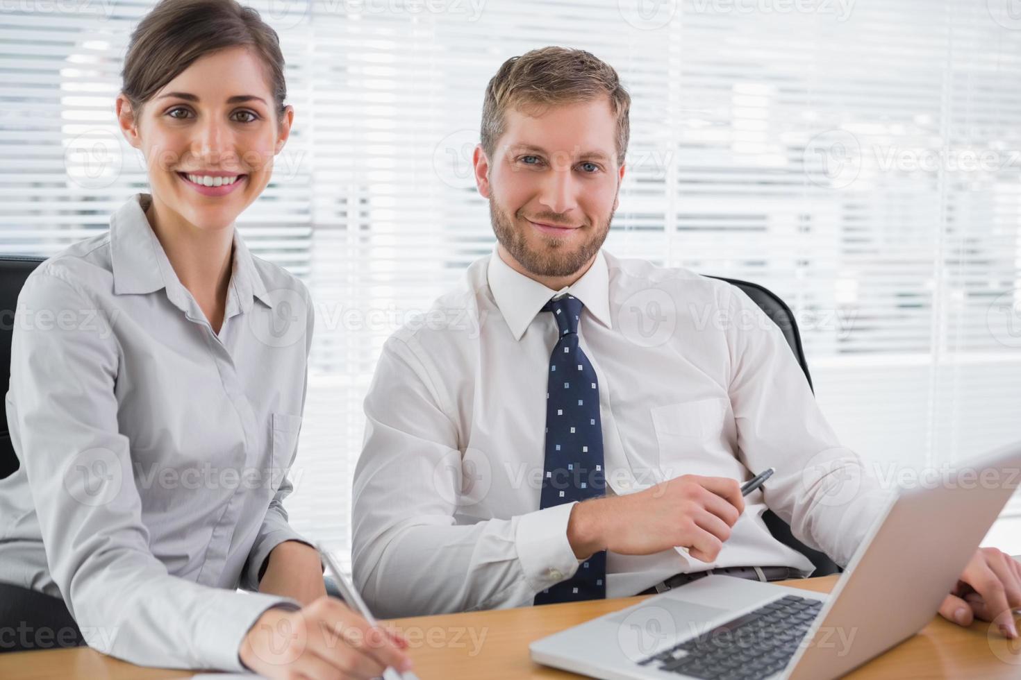 mensen uit het bedrijfsleven glimlachen op camera met laptop foto