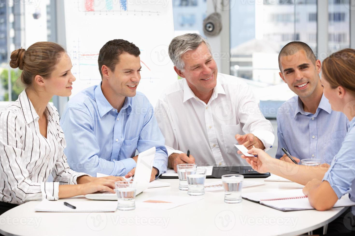 Group of business people sitting in a meeting photo