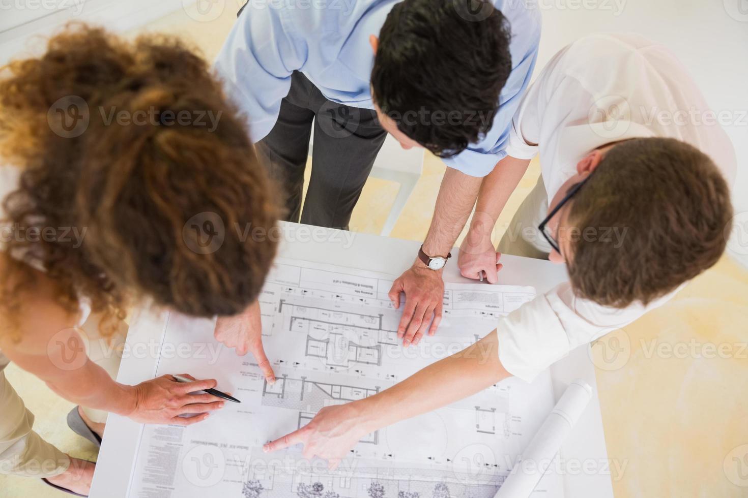 Business people analyzing blueprint photo