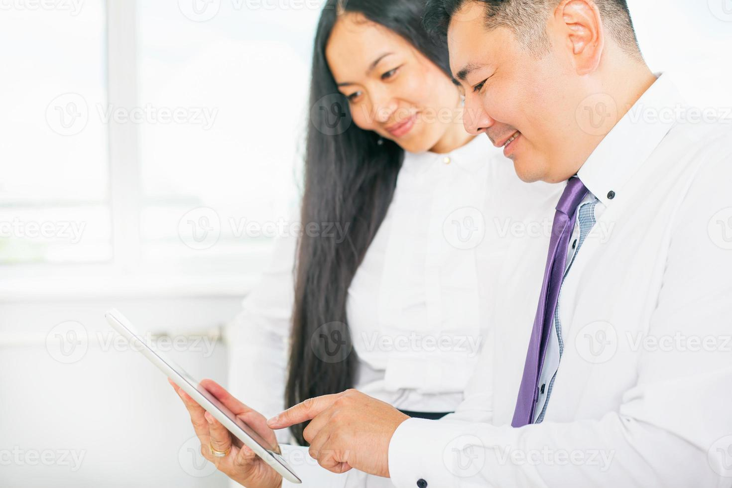 business people dressed in white using tablet pc at office photo