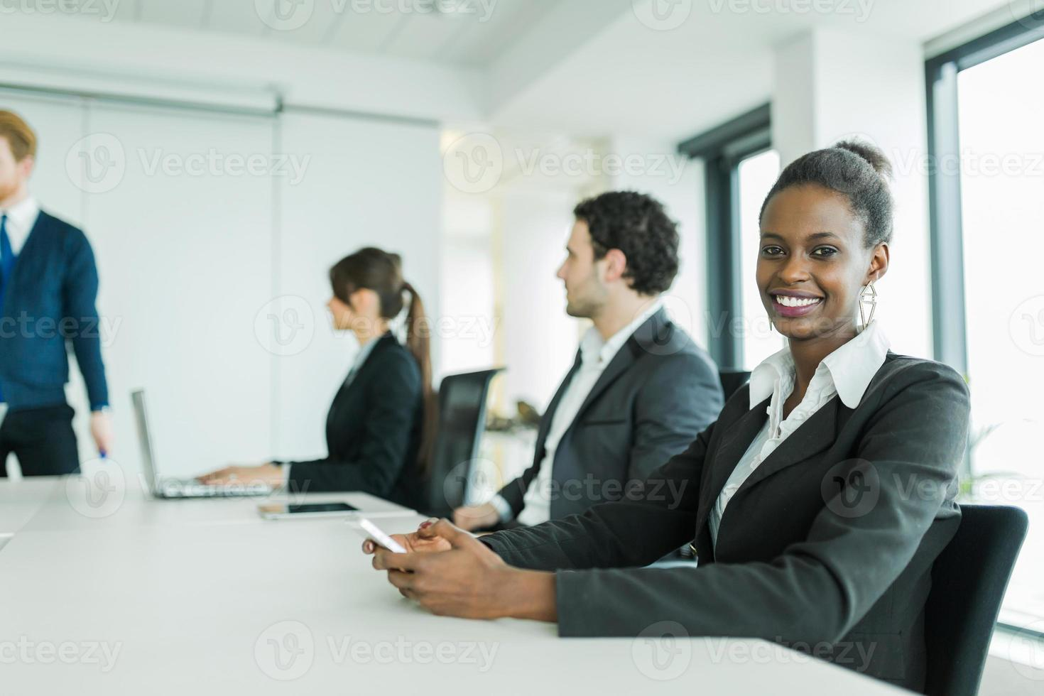 Young business people sitting at a conference table and learning photo