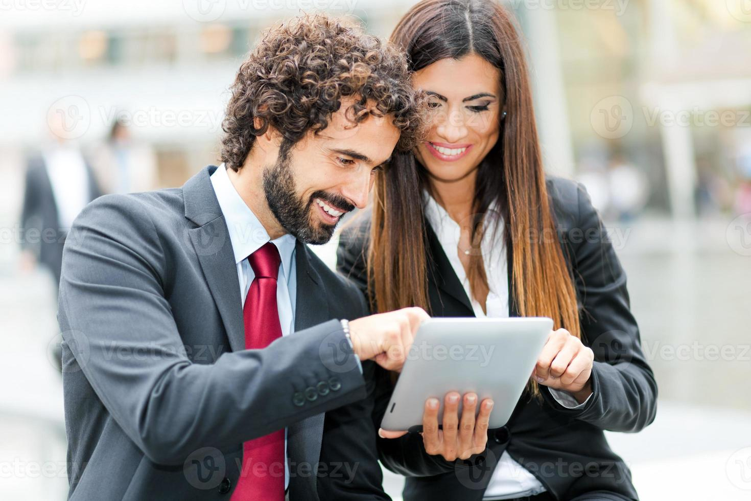 Business people using a digital tablet photo