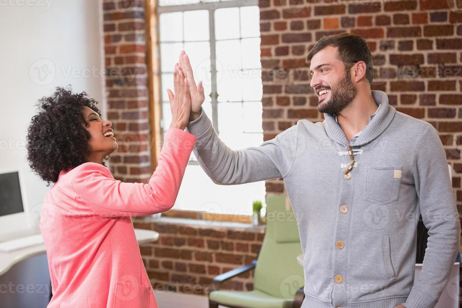 Business people high fiving at office photo