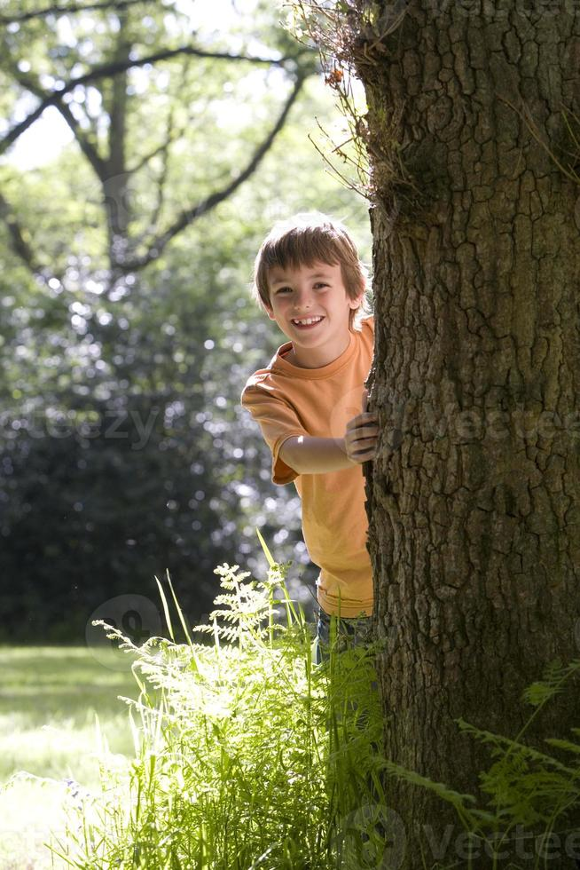 Boy (8-10) peeking out from behind tree, smiling, portrait photo