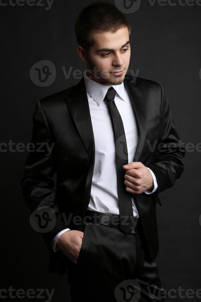 Handsome young man in suit on dark background photo