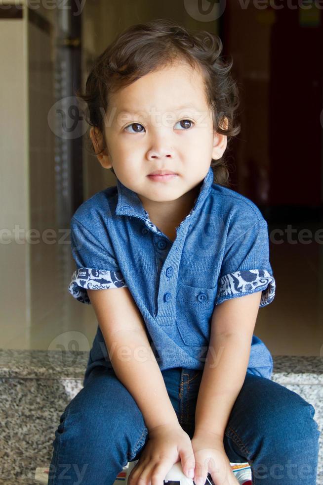 Little boy in blue jeans smiling photo