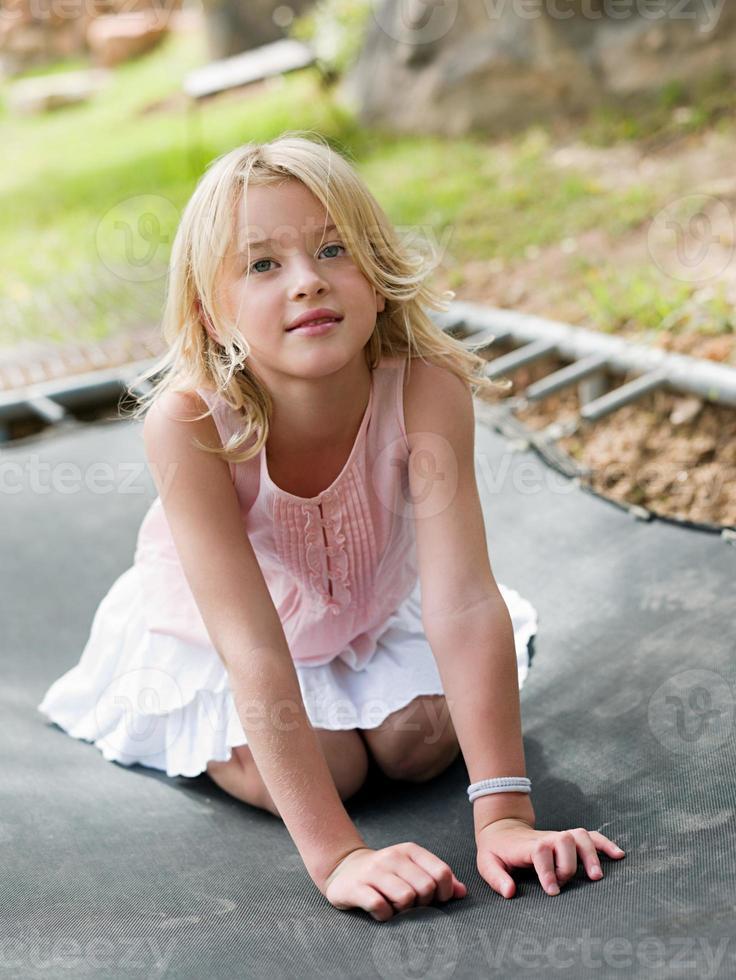 Girl kneeling on trampoline photo
