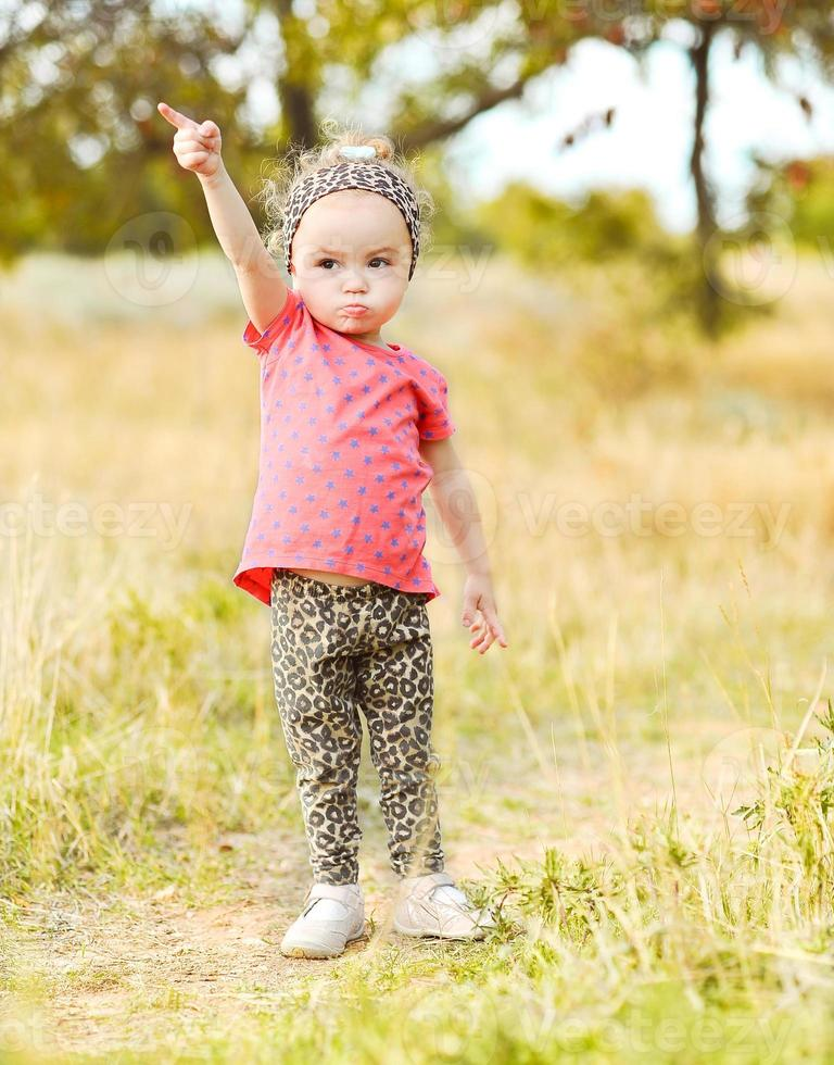Baby girl putting forefinger up outdoors photo