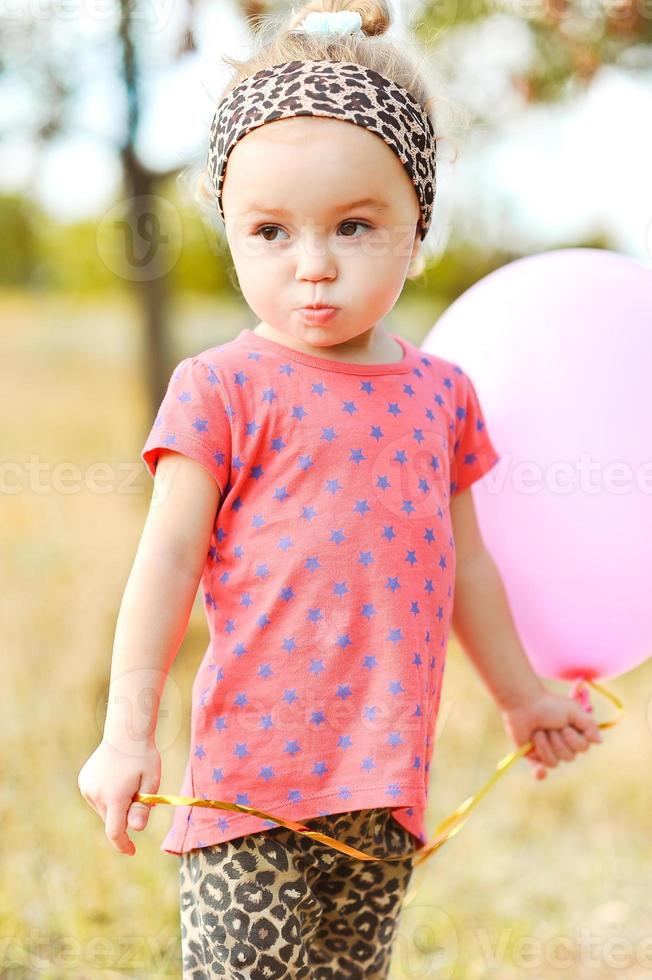 Sweet baby girl with balloon outdoors photo