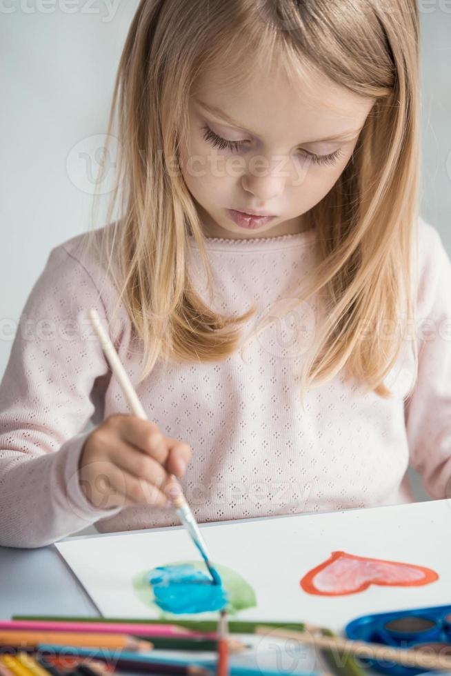 Little girl draws with paint brushes photo