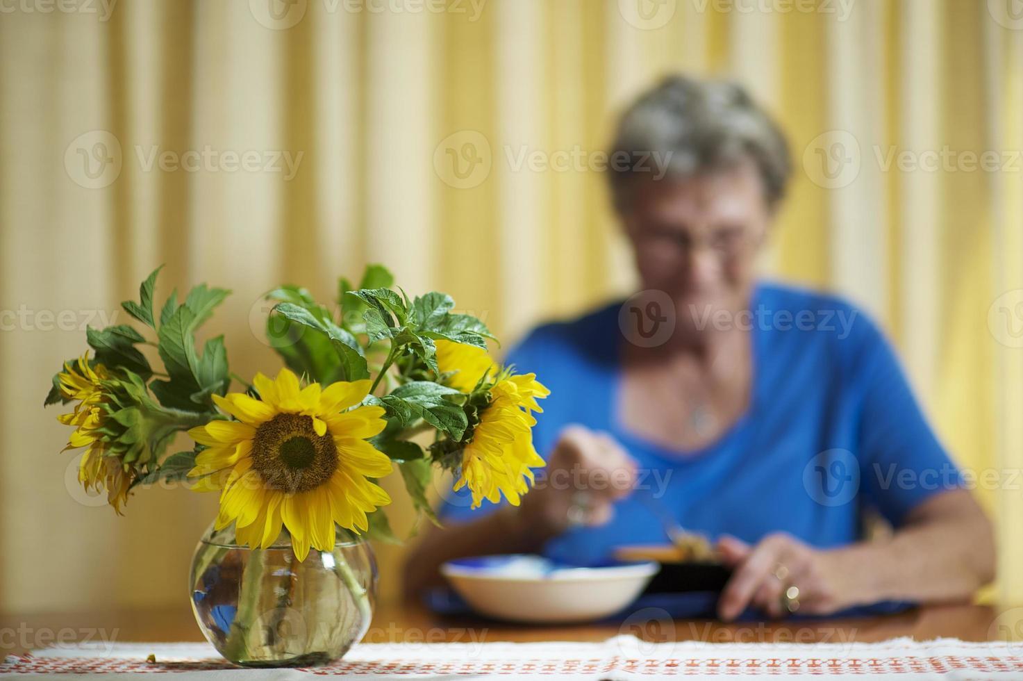 Elderly woman eating alone photo