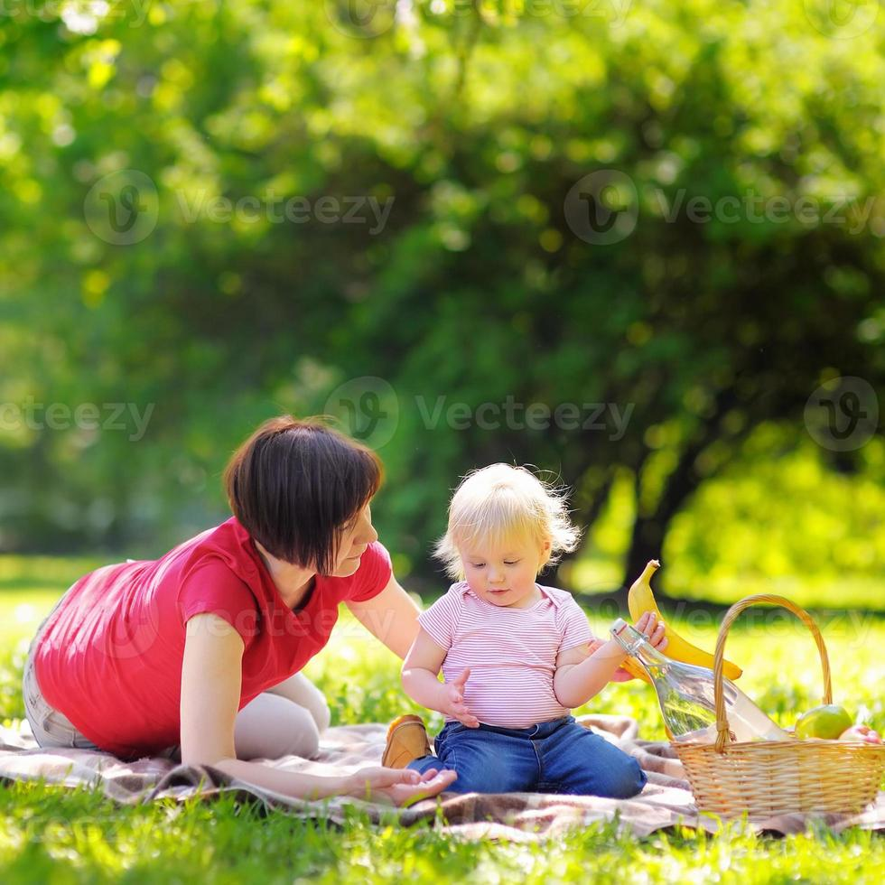 Middle aged woman and her little grandson in sunny park photo