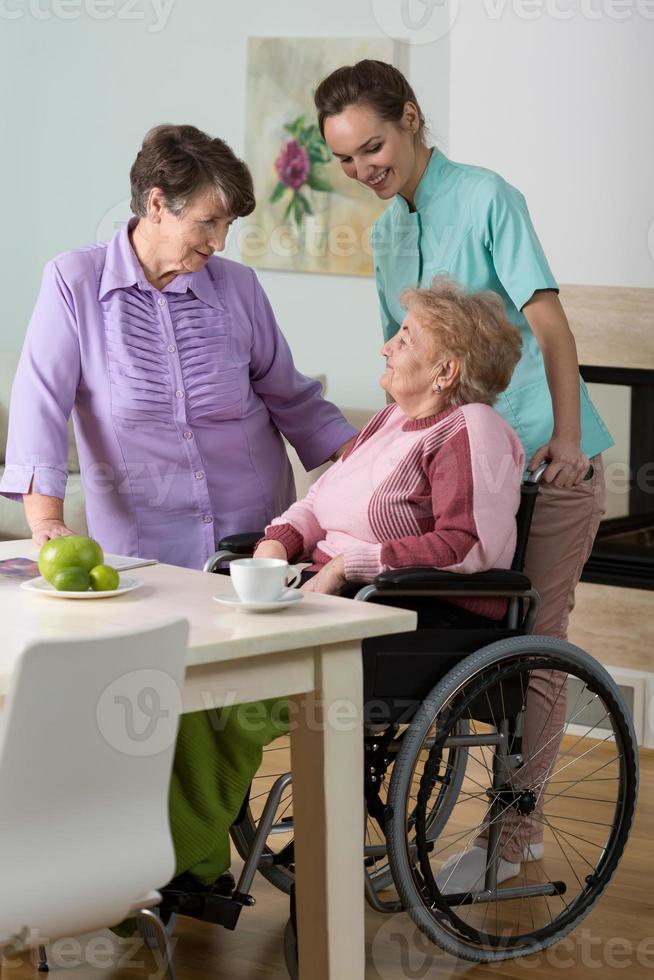Woman on wheelchair, friend and nurse photo