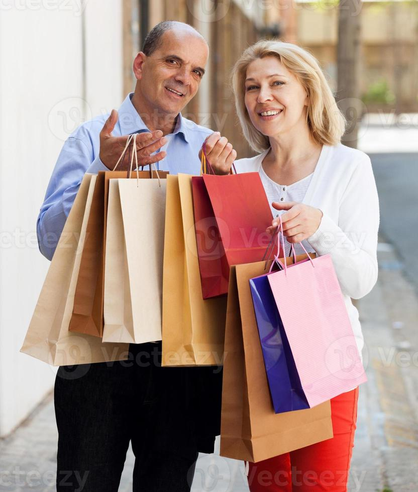 Elderly couple with shopping bags in hands and smiling photo