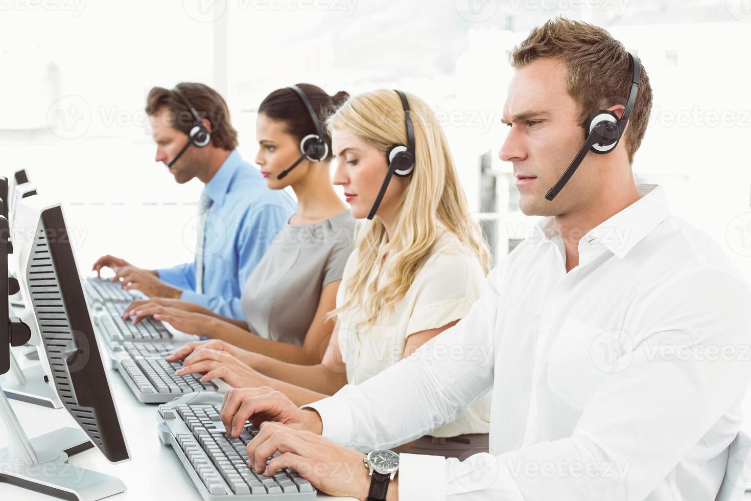 Business people with headsets using computers in office photo