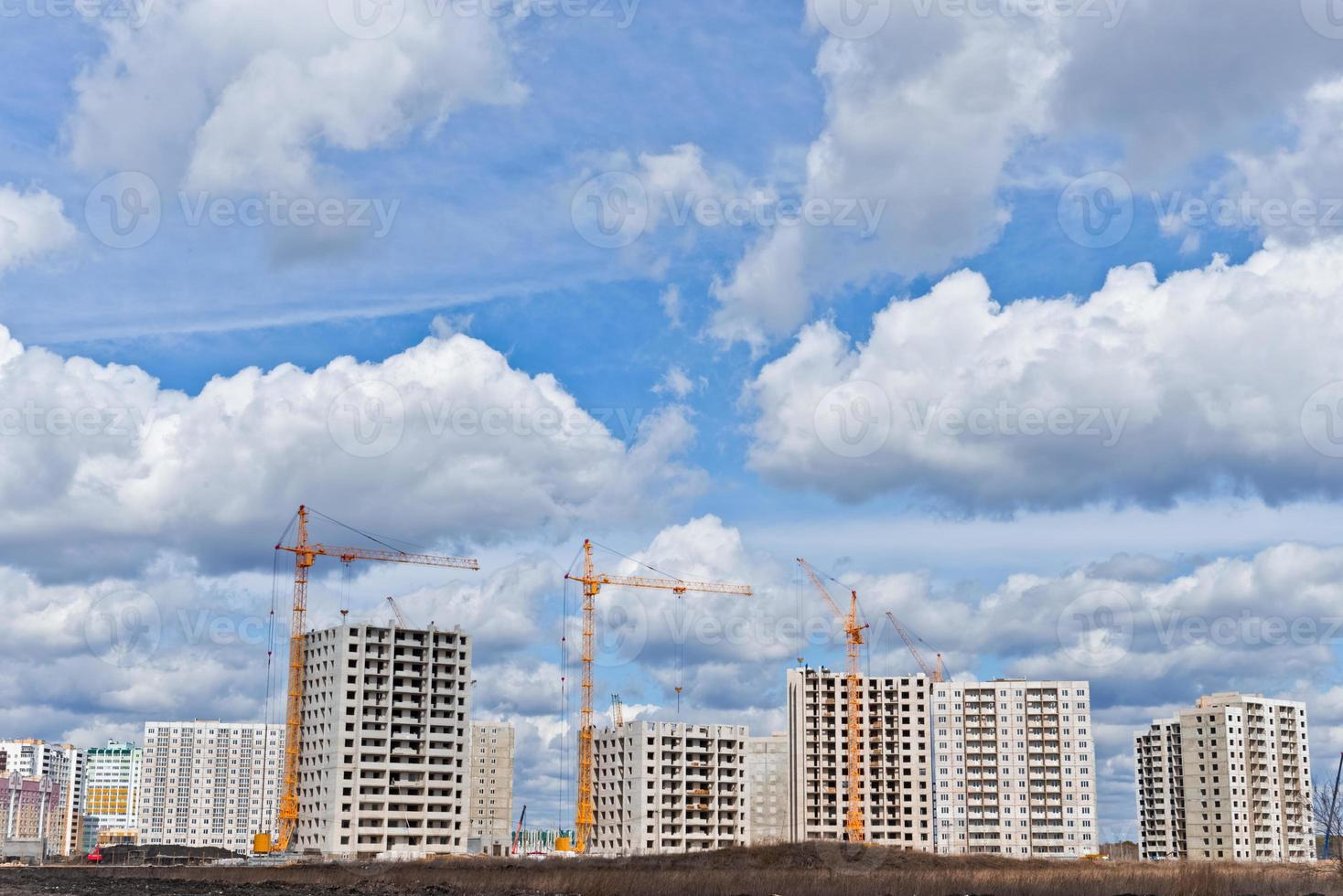 Sitio de construcción con grúas sobre fondo de cielo foto