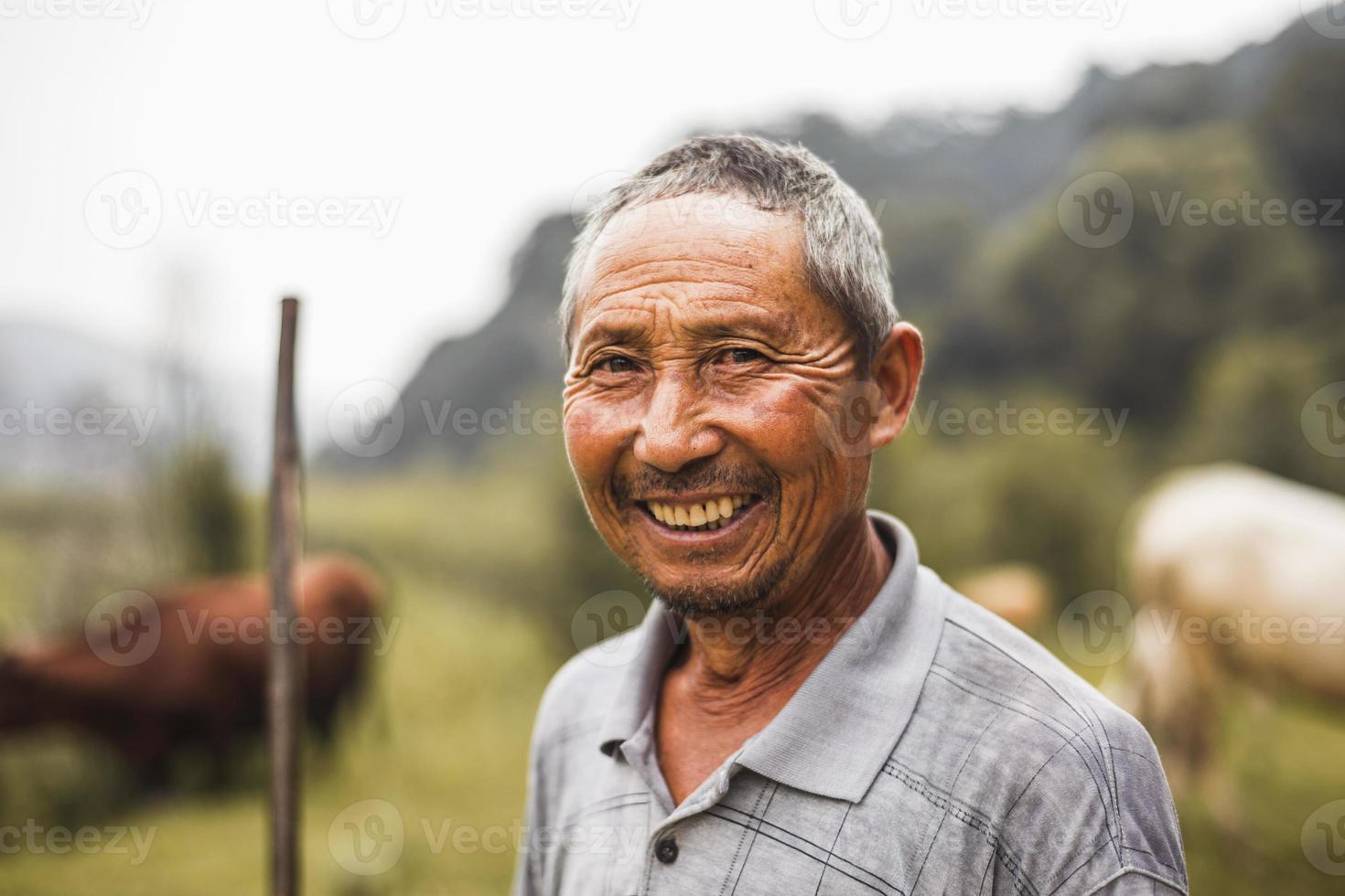 Granjero sonriente con ganado en el fondo, China rural, provincia de Shanxi foto