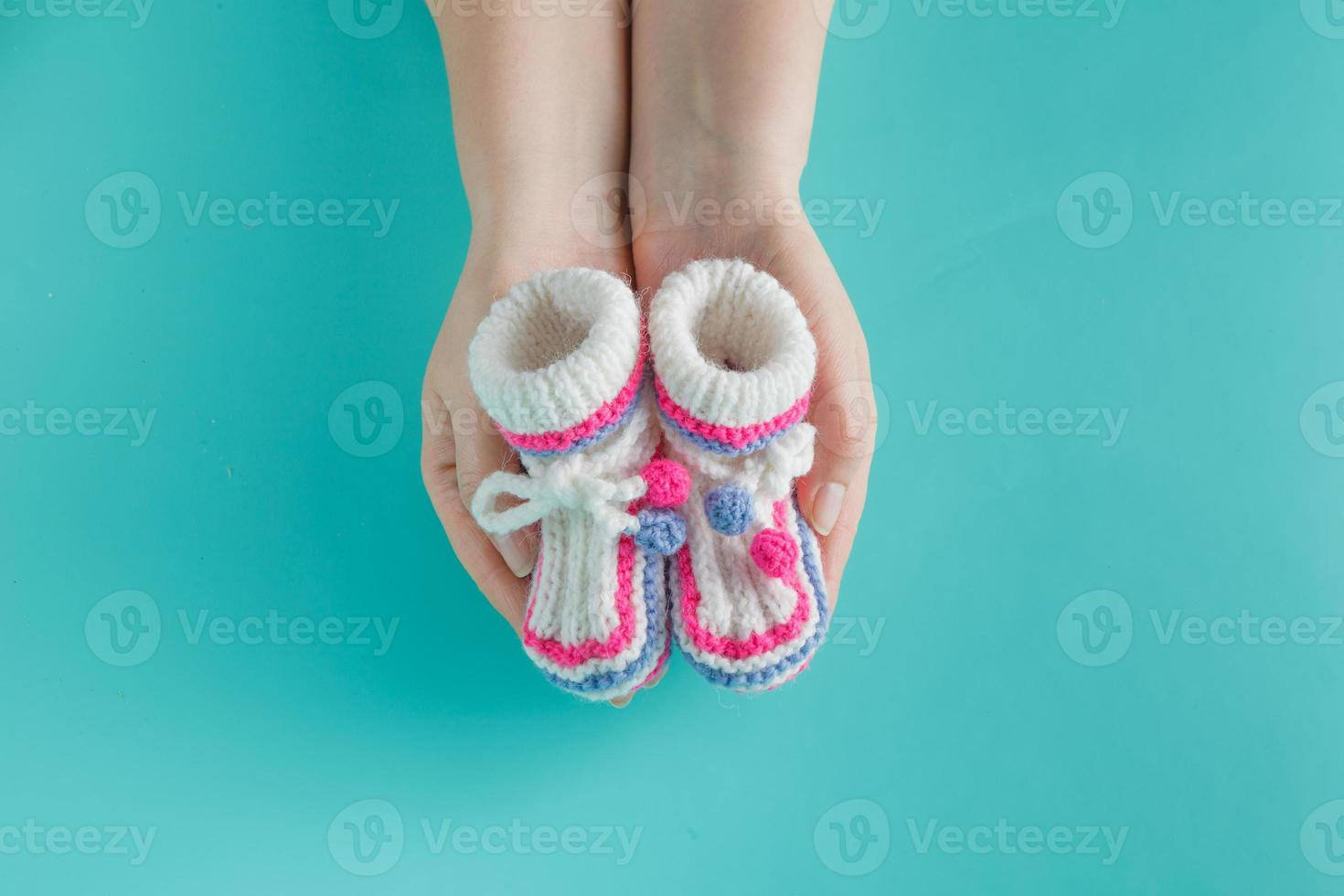 Hand holding tiny knitted booties photo