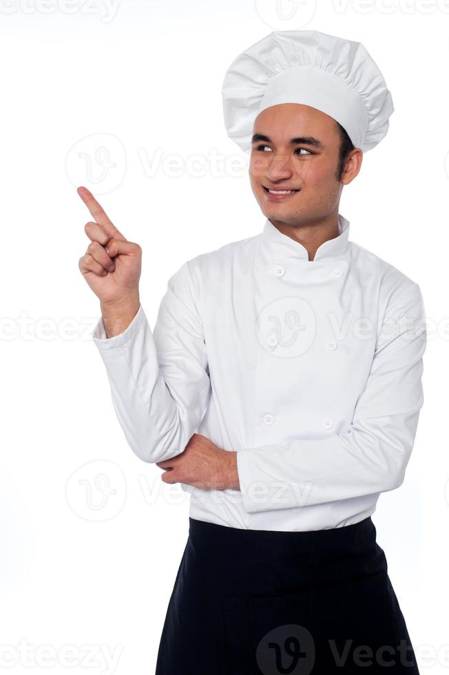 chef masculino mirando y apuntando lejos foto