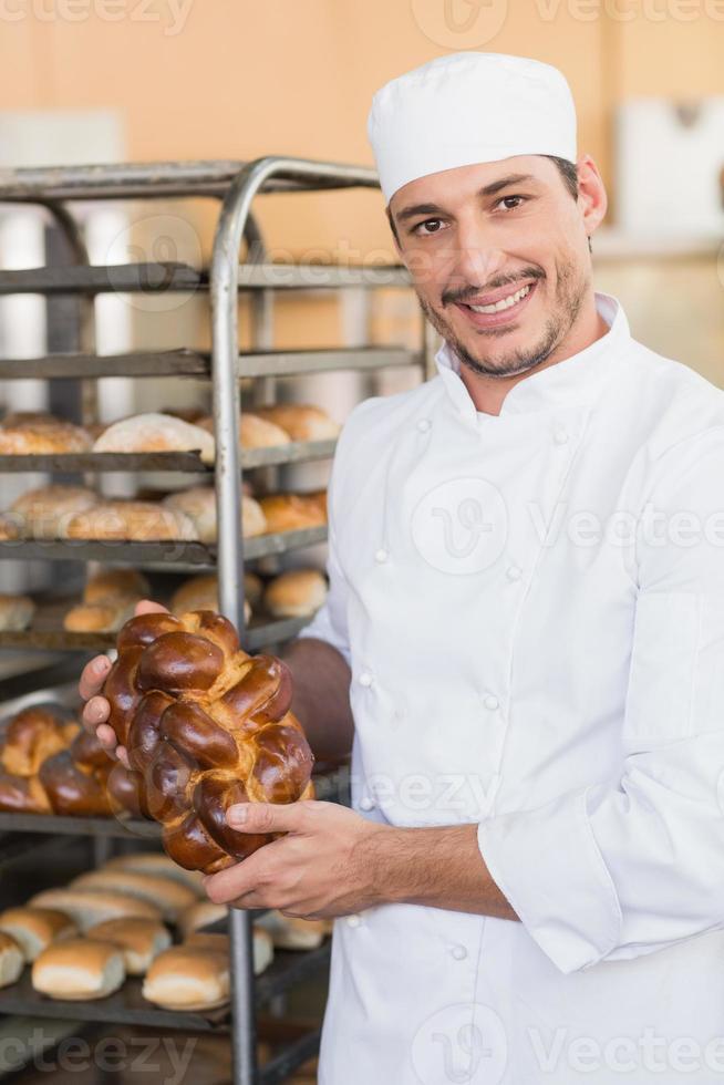 panadero sonriente con panes frescos foto