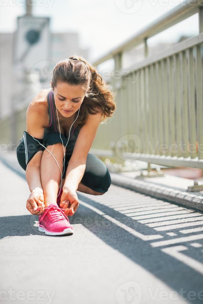fitness young woman tying shoelaces in the city photo