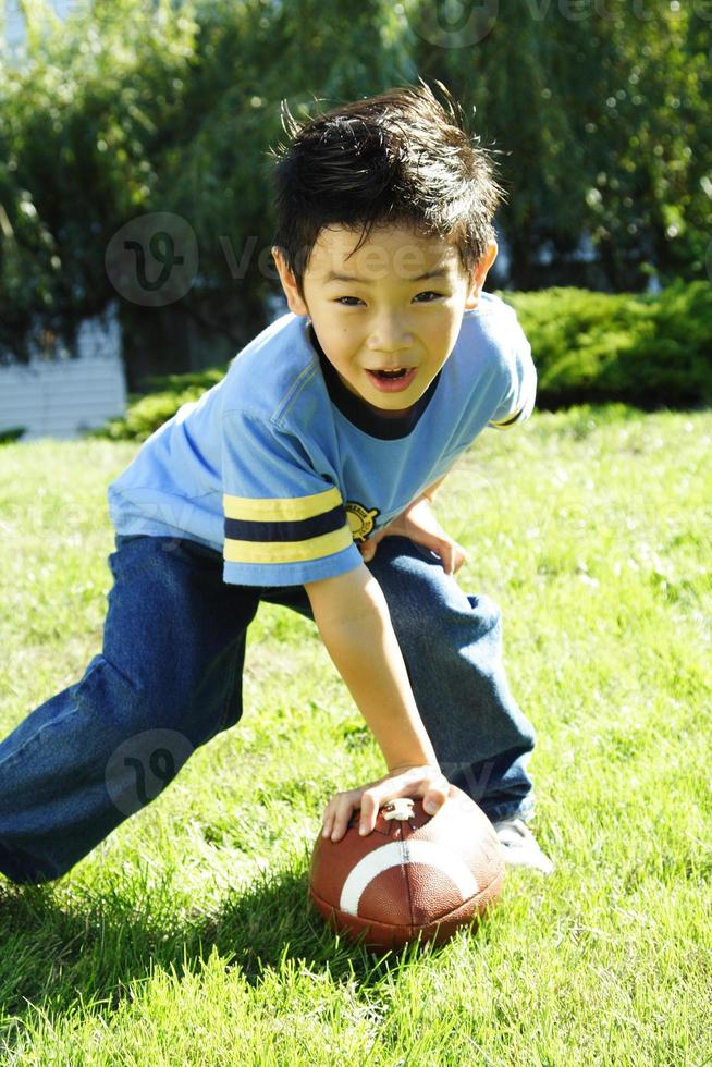Young Asian boy playing football photo
