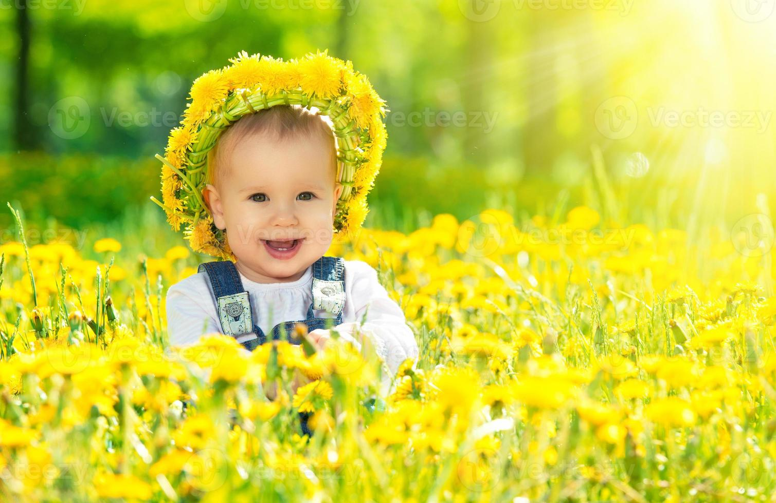 happy baby girl in wreath on  meadow with yellow flowers photo
