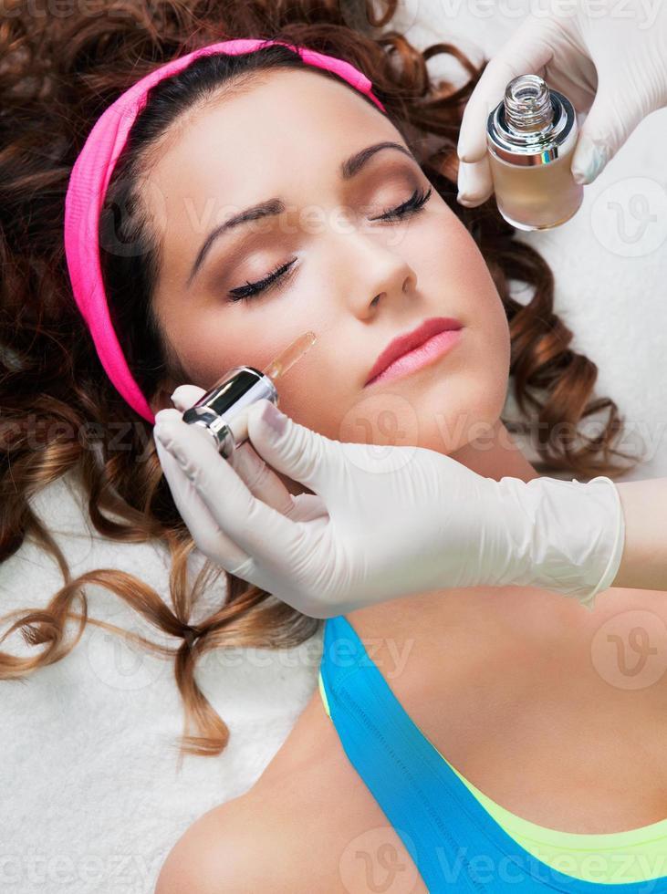 Mujer recibiendo tratamiento facial en el centro de spa médico foto
