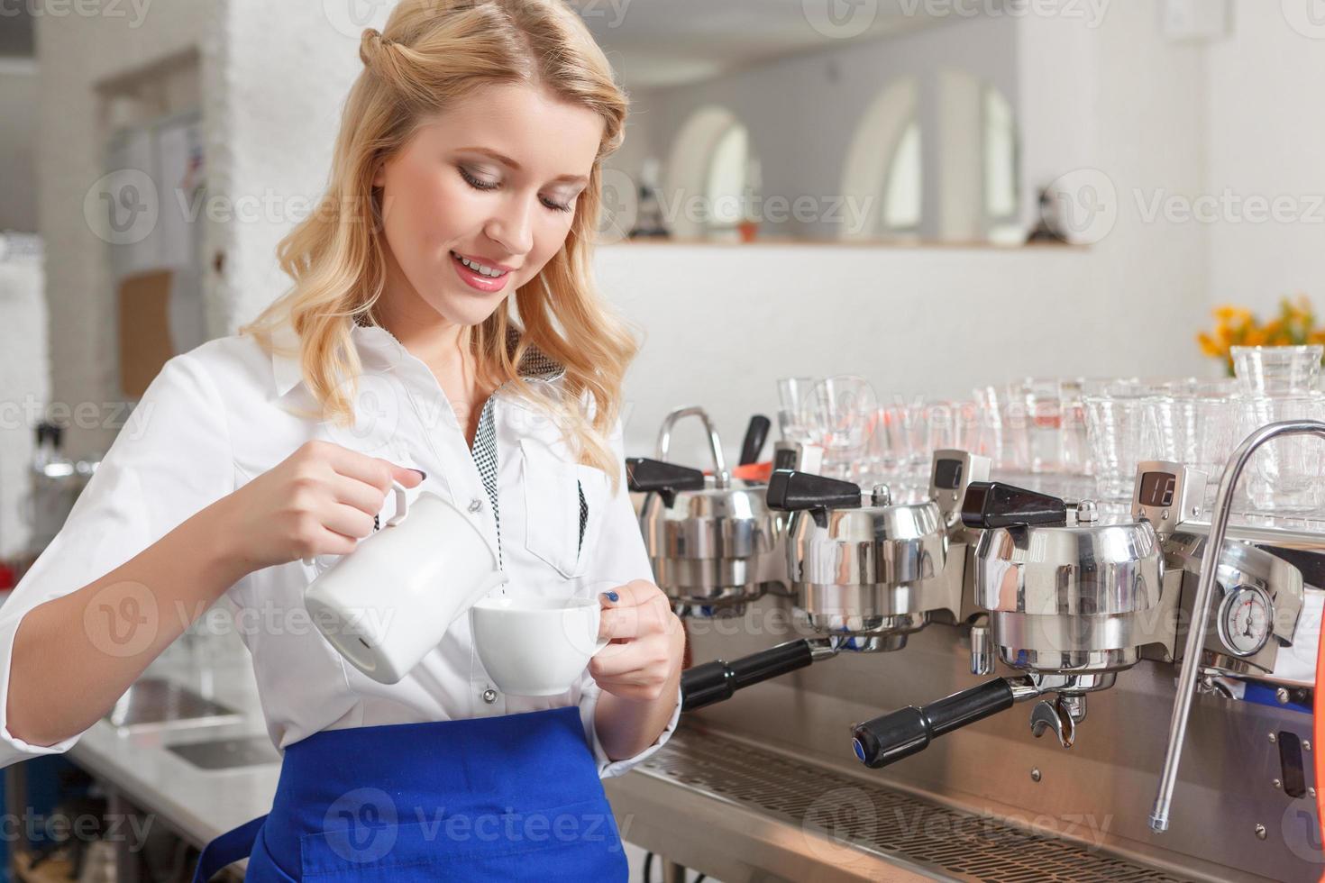 bonita mujer barista vertiendo un poco de leche en la taza foto