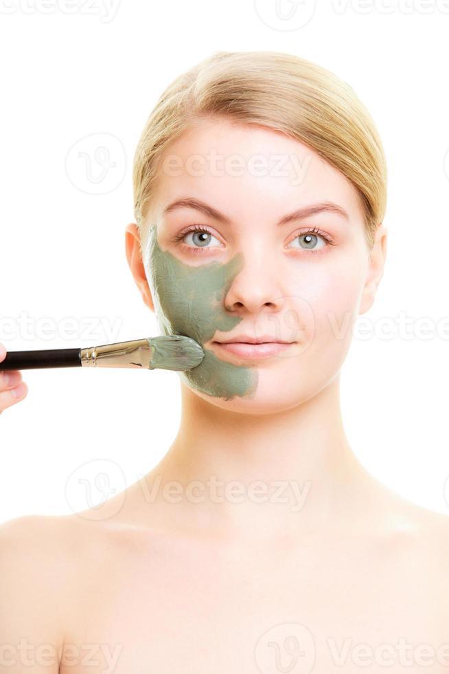 protección de la piel. Mujer aplicando mascarilla de barro en la cara. foto