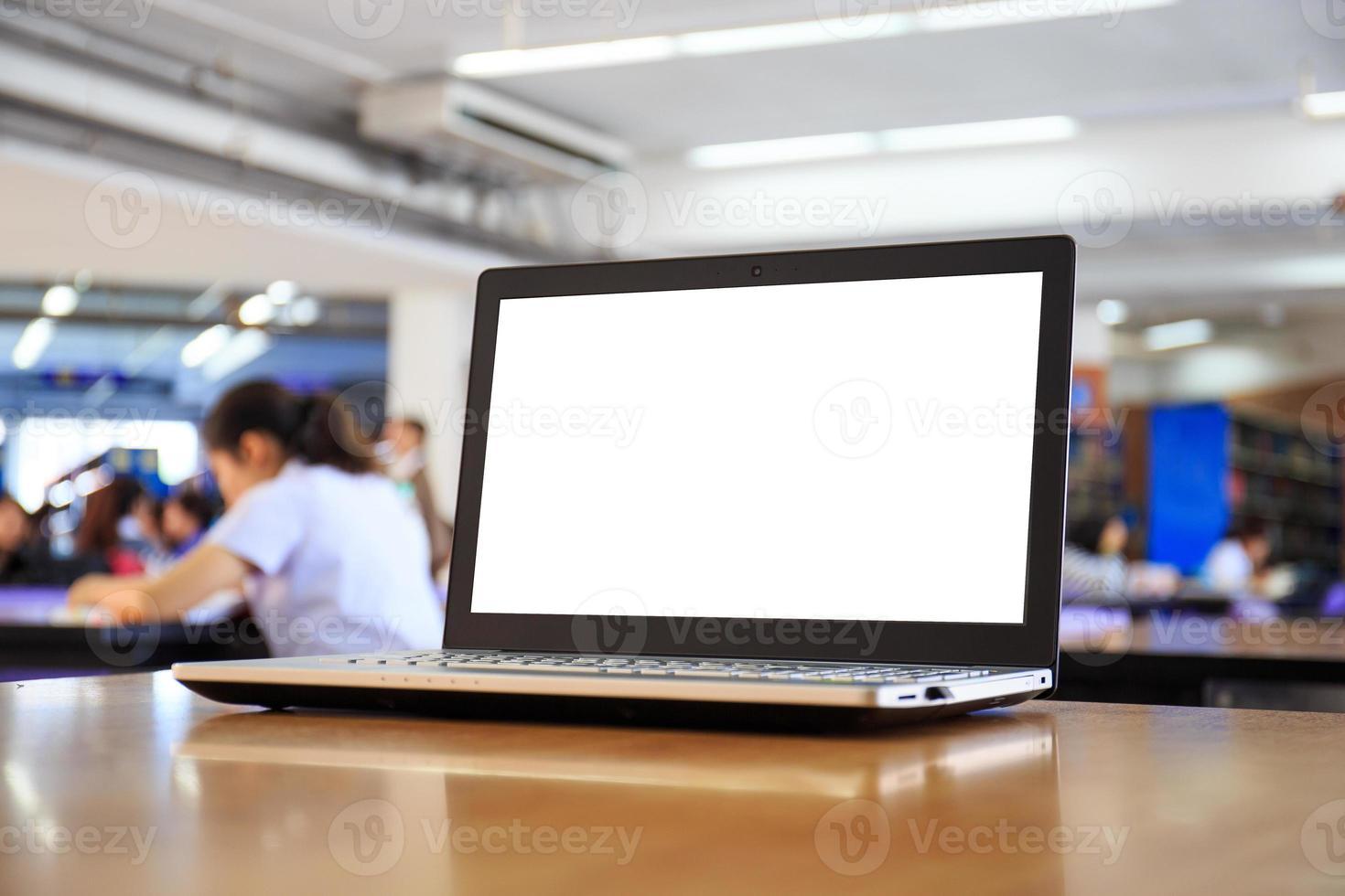 Portátil con pantalla en blanco sobre la mesa en la biblioteca foto