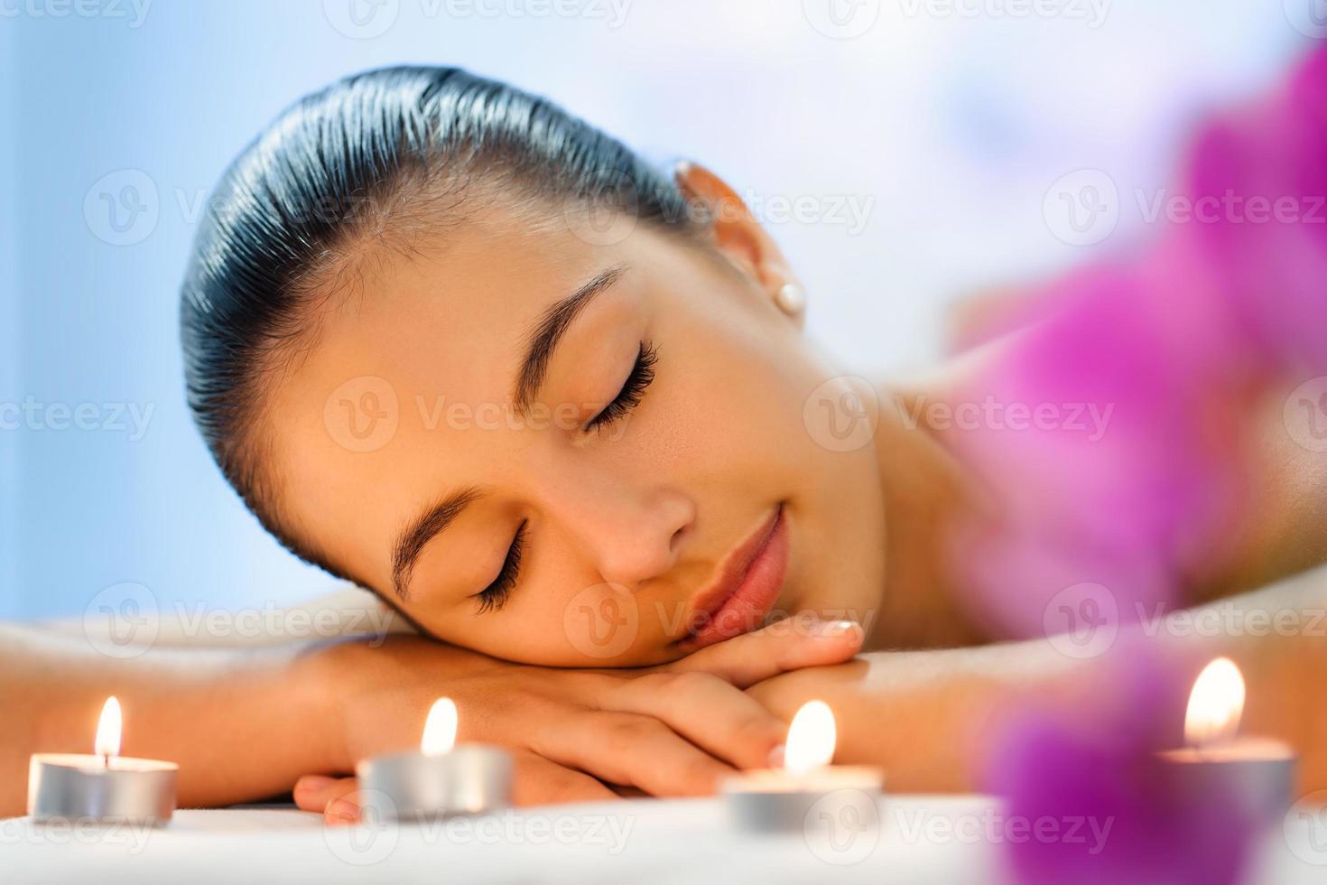 Mujer joven relajante en luz de las velas atenuada después del masaje. foto
