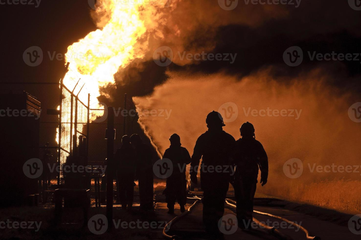 silhouette of firefighters in action by night photo