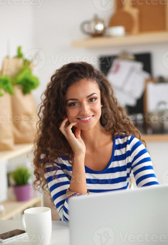 Smiling young woman with coffee cup and laptop in the photo