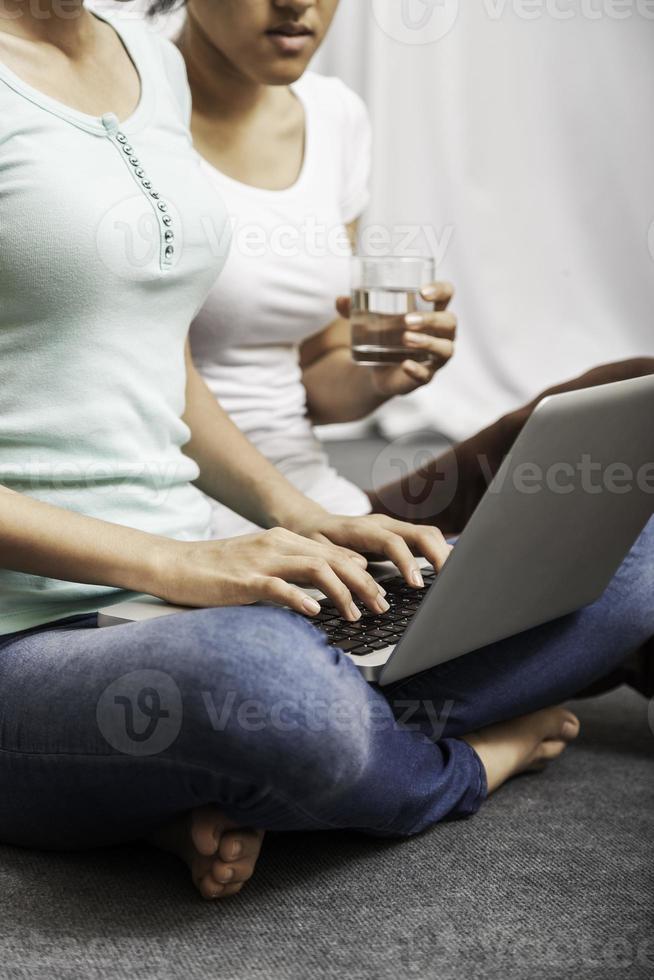 mujeres jóvenes sentados y usando laptop foto