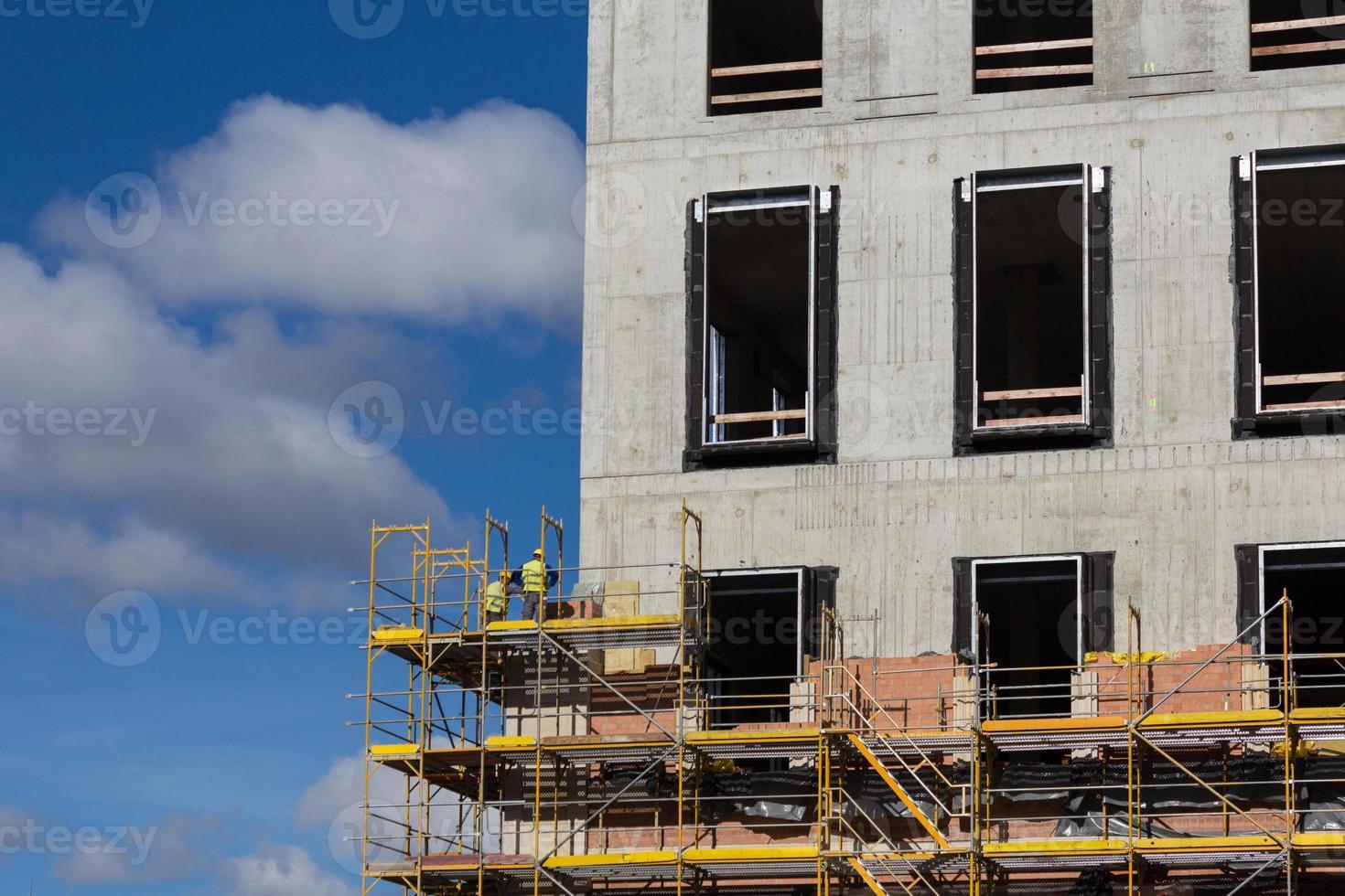trabajadores de la construcción en andamios - construcción de fachadas constructi foto