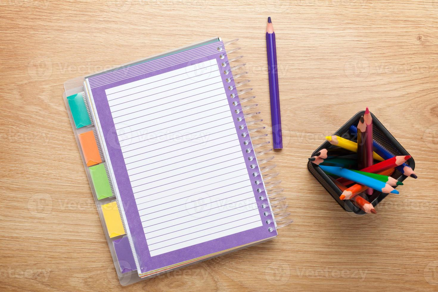 Office table with blank notepad and colorful pencils photo