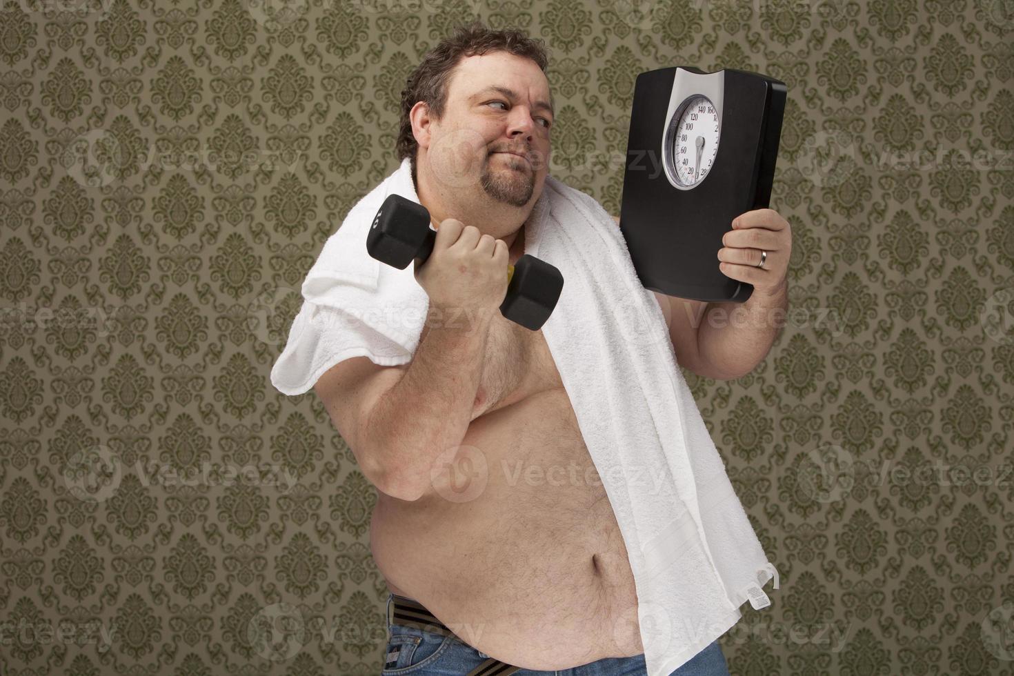 Hombre con sobrepeso sosteniendo escalas trabajando duro para perder peso foto