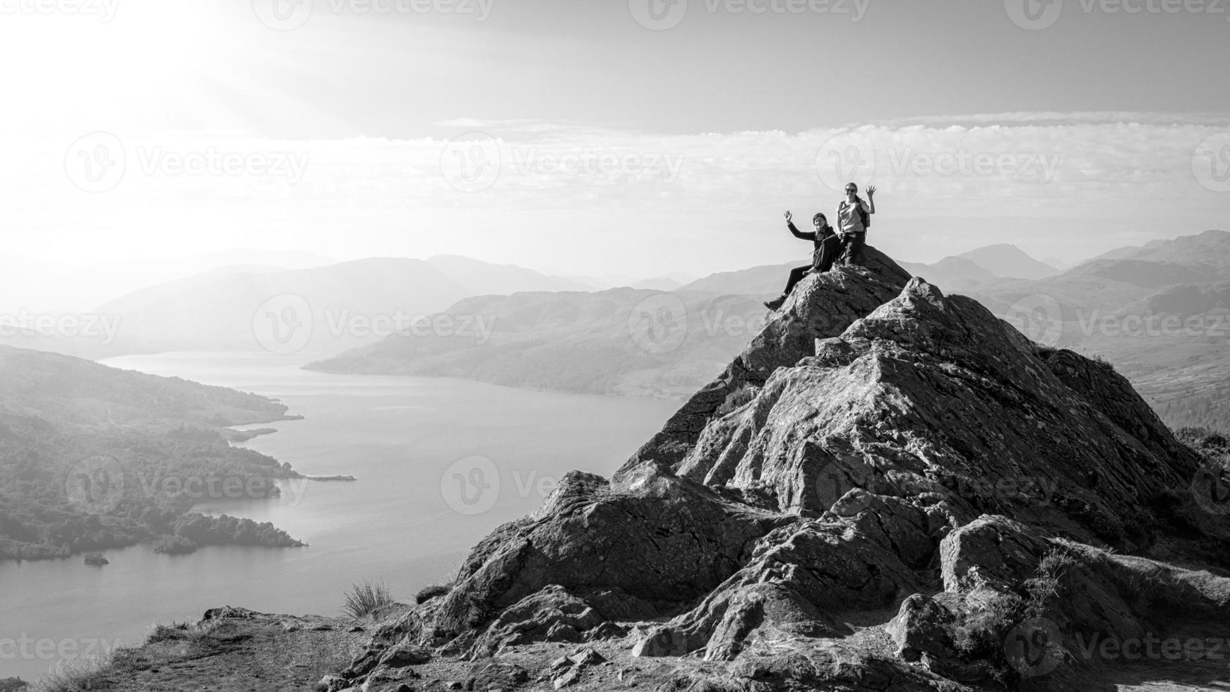 Excursionistas en la cima de la montaña disfrutando de la vista, Loch Katrine, Escocia foto