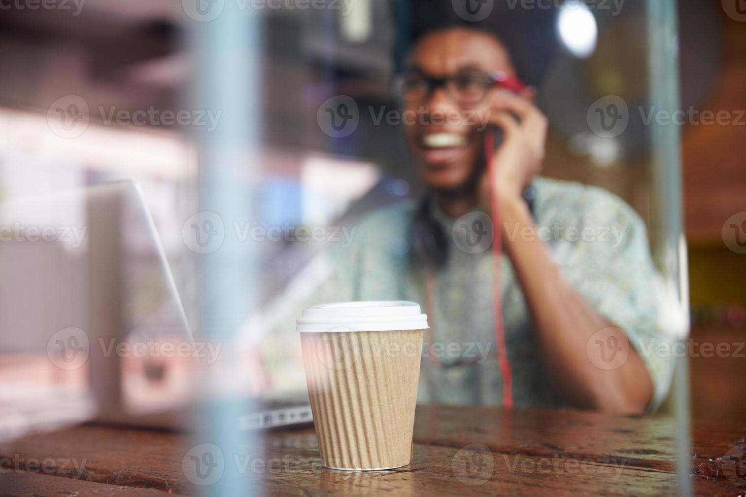 Hombre de negocios con teléfono trabajando en la computadora portátil en la cafetería foto